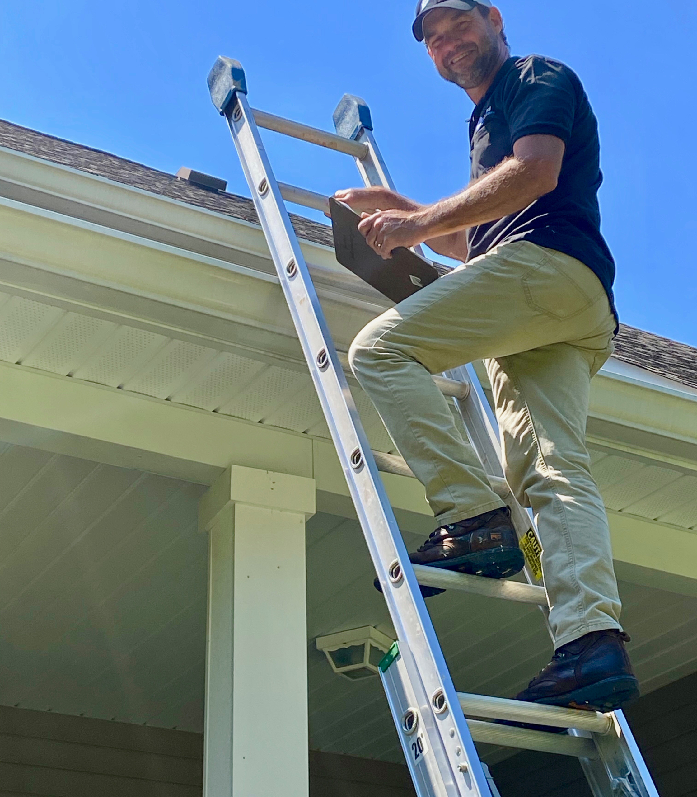Owner of Universal Home Inspections, Mike Makely, inspecting the roof of a home.