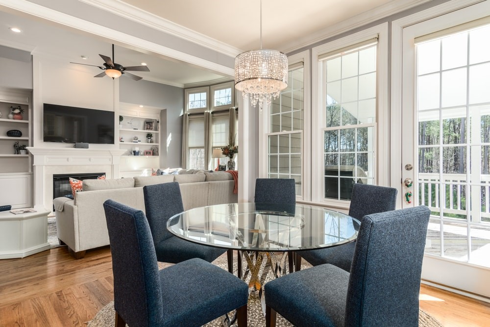 A well-lit dining room with a clear round table and blue chairs