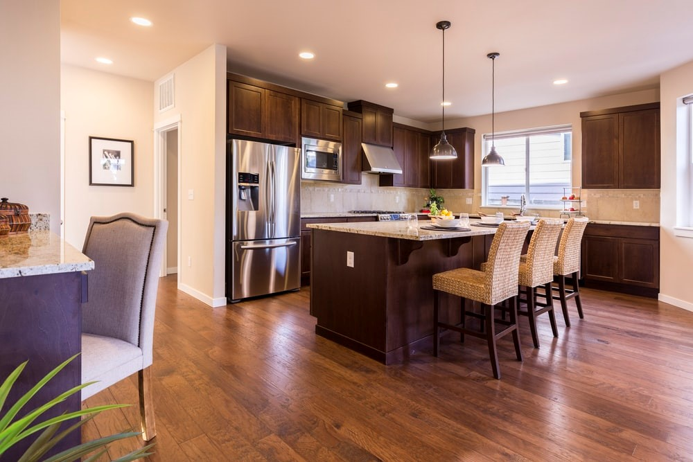 A brown and beige kitchen interior with shiny, wood floors