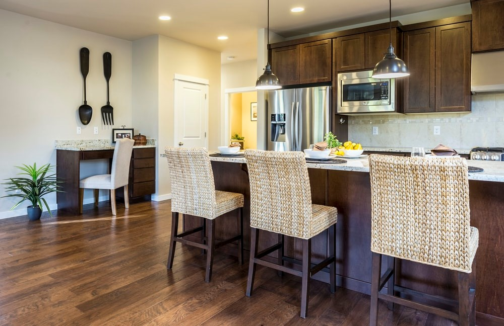 A modern kitchen with wooden chairs and hanging lights